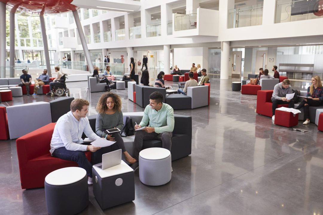 Campus building with students sitting in the lobby